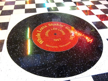 """At the Denver location, guests are welcomed by a giant-sized reproduction of a Jerry Lee Lewis record, """"Who Lotta Shakin Goin' On,"""" set into the tile floor."""